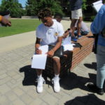A cadet takes diligent notes outside during a tour of UTC.