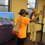 A cadet wearing virtual reality gear pets a manatee visible on a screen.